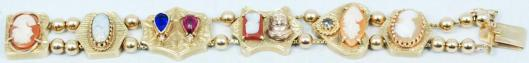 A 14 K yellow gold slider bracelet with 6 cameo charms, opal, sapphire and ruby.  Eliteauction.com